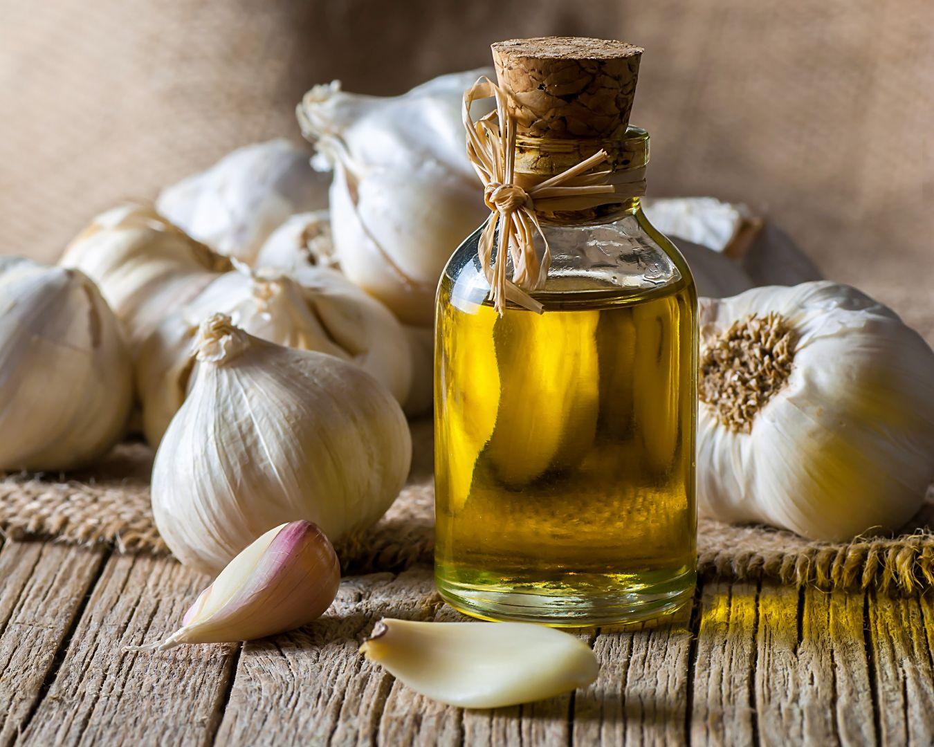 bote de aceite de oliva y dientes de ajo