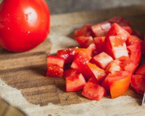 Añadimos a la sartén uno de los tomates cortados en dados