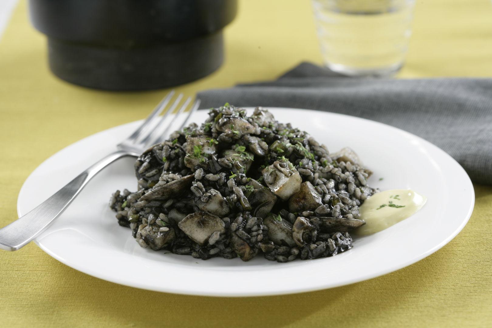 Arroz negro de sepia y chirlas sobre un plato blanco