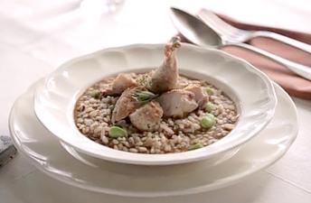 Delicioso arroz caldoso con perdiz y morcilla en plato blanco