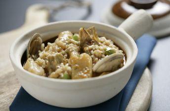 Exquisito arroz meloso de almejas, bacalao y alcachofas